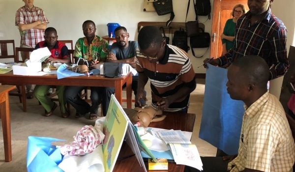 Photo:Jonas (pictured in foreground) observing a trainee on proper umbilical cord care after birth.